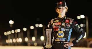 Jesse Love, driver of the No. 19 NAPA Power Premium Plus Toyota, poses for a photo with the ARCA Menards Series West championship trophy at Phoenix Raceway in Avondale, Arizona, on Nov. 7, 2020 (Christian Petersen/Getty Images)