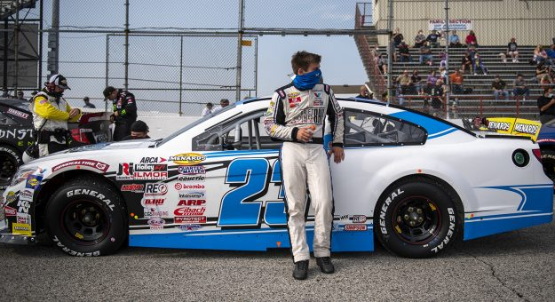 Bret Holmes, driver of the No. 23 Holmes II Excavation Chevrolet, rests on his car before the Royal Truck & Trailer 200 for the ARCA Menards Series at Toledo Speedway in Toledo, Ohio, on Sept. 12, 2020. (Nic Antaya/ARCA Racing)