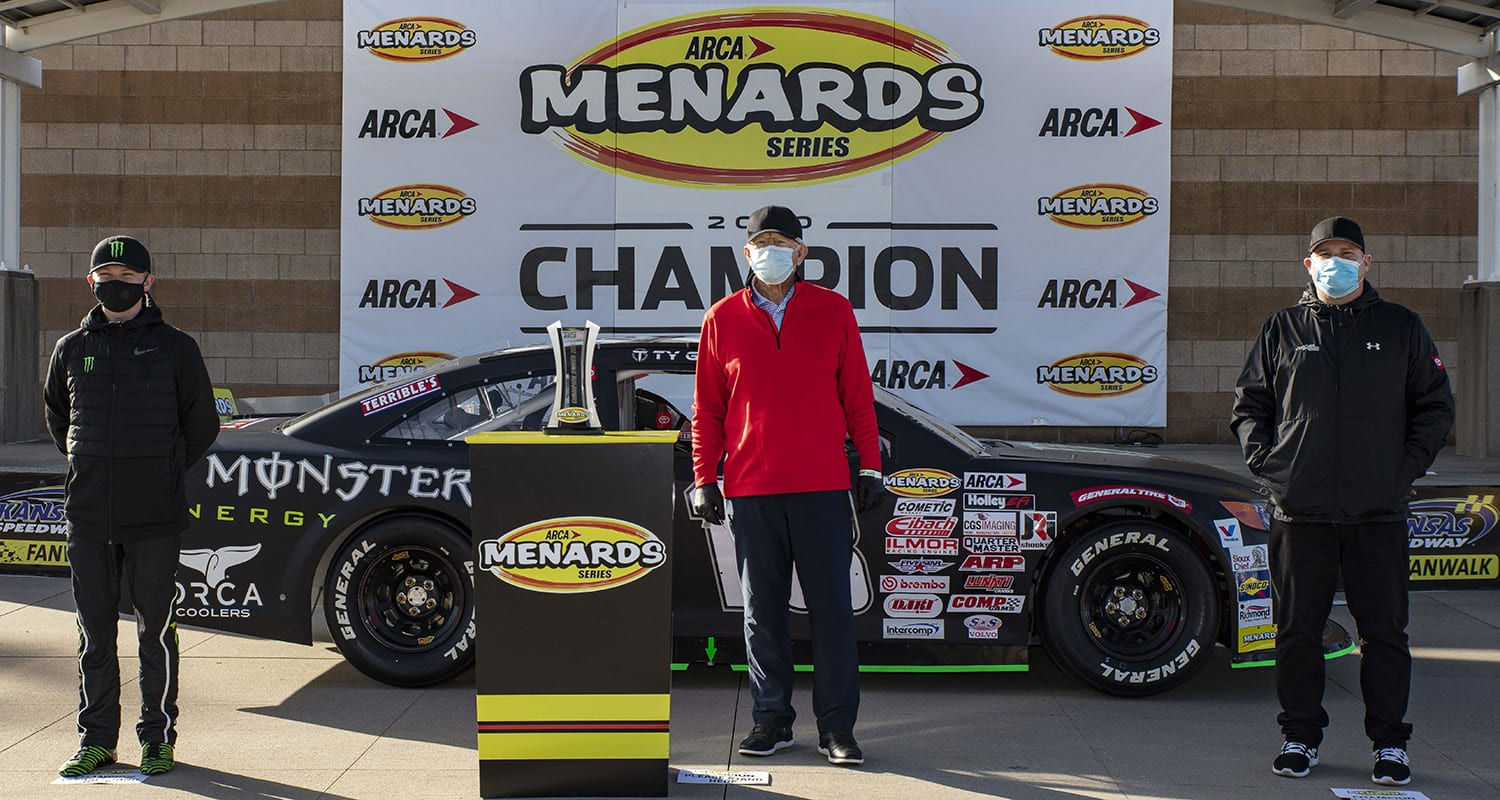 Ty Gibbs (left), driver of the No. 18 Monster Energy/Terrible Herbst-ORCA Toyota, stands with his grandfather/team owner Joe Gibbs (middle) and father/car owner Coy Gibbs (right) with the 2020 ARCA Menards Series owner's champiomship trophy before the Speediatrics 150 at Kansas Speedway in Kansas City, Kansas, on Oct. 16, 2020. (Barry Cantrell/ARCA Racing)